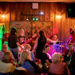 Live band playing on O'Michael's stage with dancers and diners.