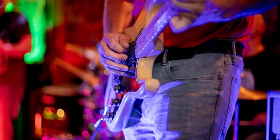 Close-up of musician, lit up with a blue light, playing guitar.