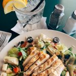 O'Michael's Pub & Grill chicken salad with olives on plate with glass of lemon water.