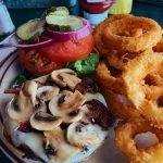 Mushroom burger and onion rings on plate.
