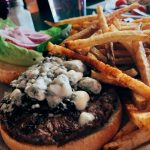 Plate with spicy bleu cheeseburger and fries