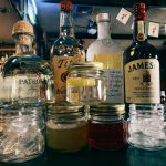 Bottles of liquor and mixed drinks on a bar.
